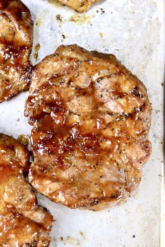 Peach BBQ glazed pork steaks on a baking sheet with grill marks, close up view