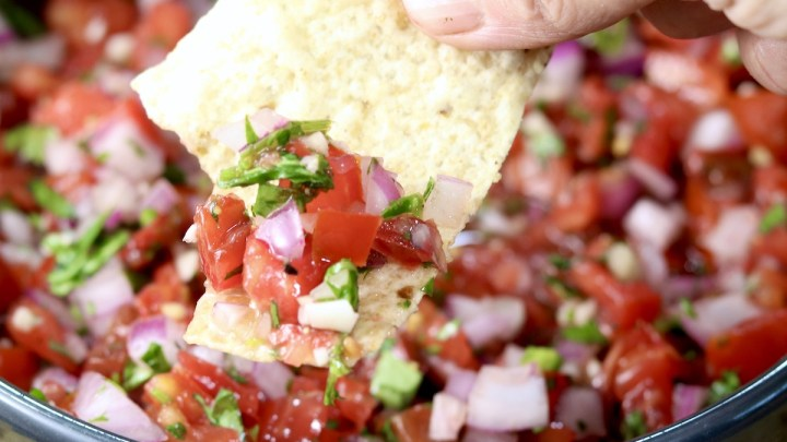 Pico de Gallo in a black bowl, dipped with a tortilla chip