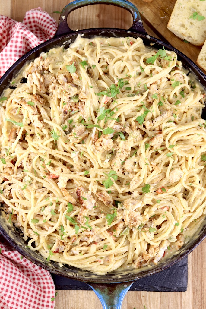 Skillet of cheesy chicken spaghetti garnished with parsley