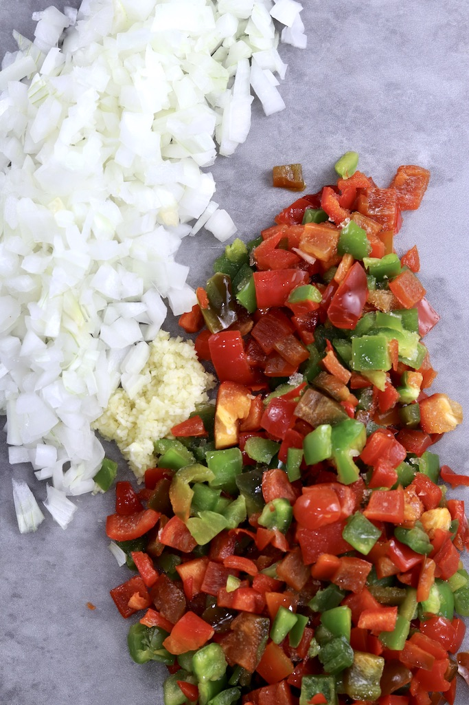 Diced onions, garlic and red and green peppers on a gray cutting board