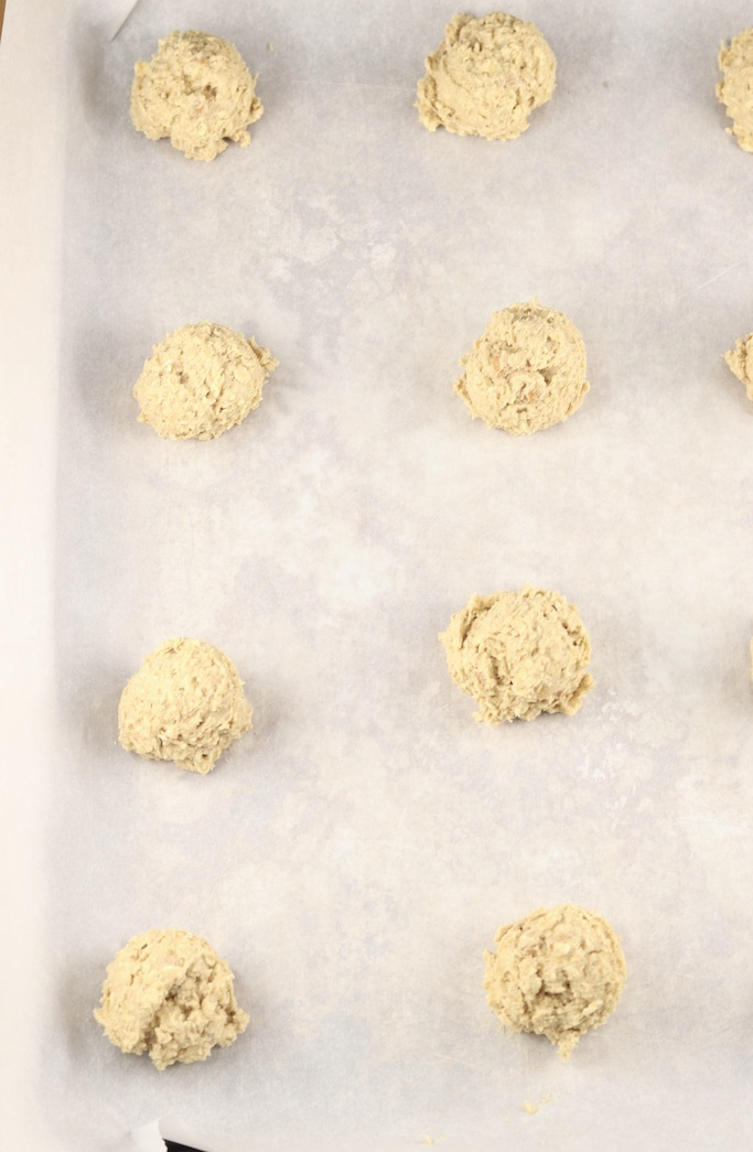 Cookie dough balls on white parchment paper lined baking sheet -overhead view