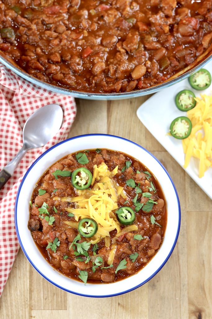 Bowl of chili with cheese, jalapenos, pan of chili above on a wood table