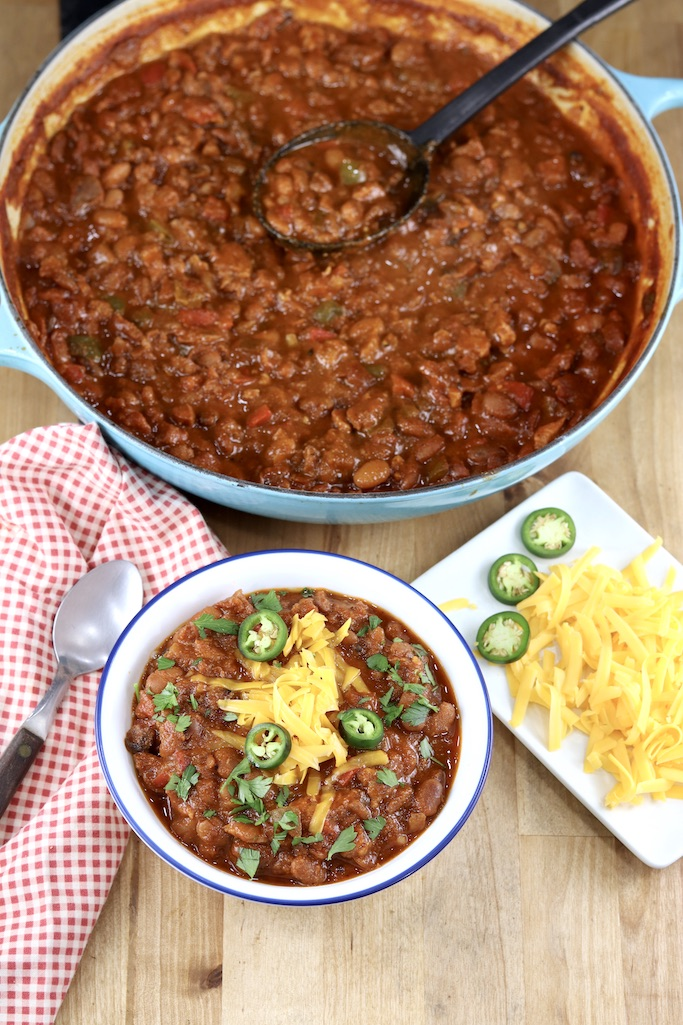 Smoked Pork Chili served in a bowl, dutch oven with chili, garnish plate with cheese and jalapenos