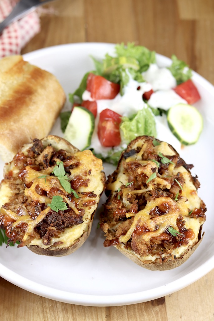 Smoked Pork topped twice baked potatoes on a white plate with salad and bread