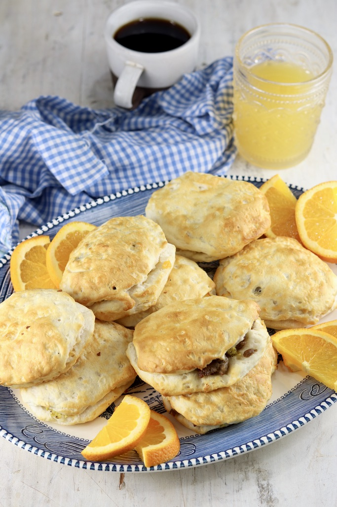 Platter of sausage biscuits with coffee and orange juice