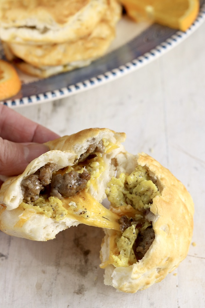 biscuit split in half with melted cheese, eggs and sausage