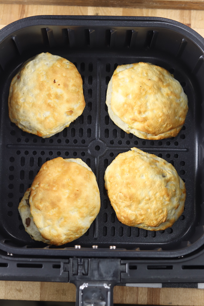 air fryer basket with cooked biscuit sandwiches