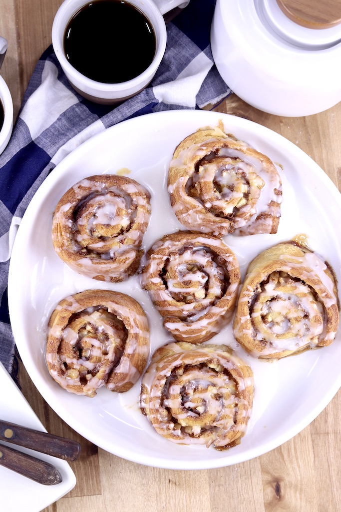 Cinnamon rolls on a white plate, with cup of coffee and small coffee pot