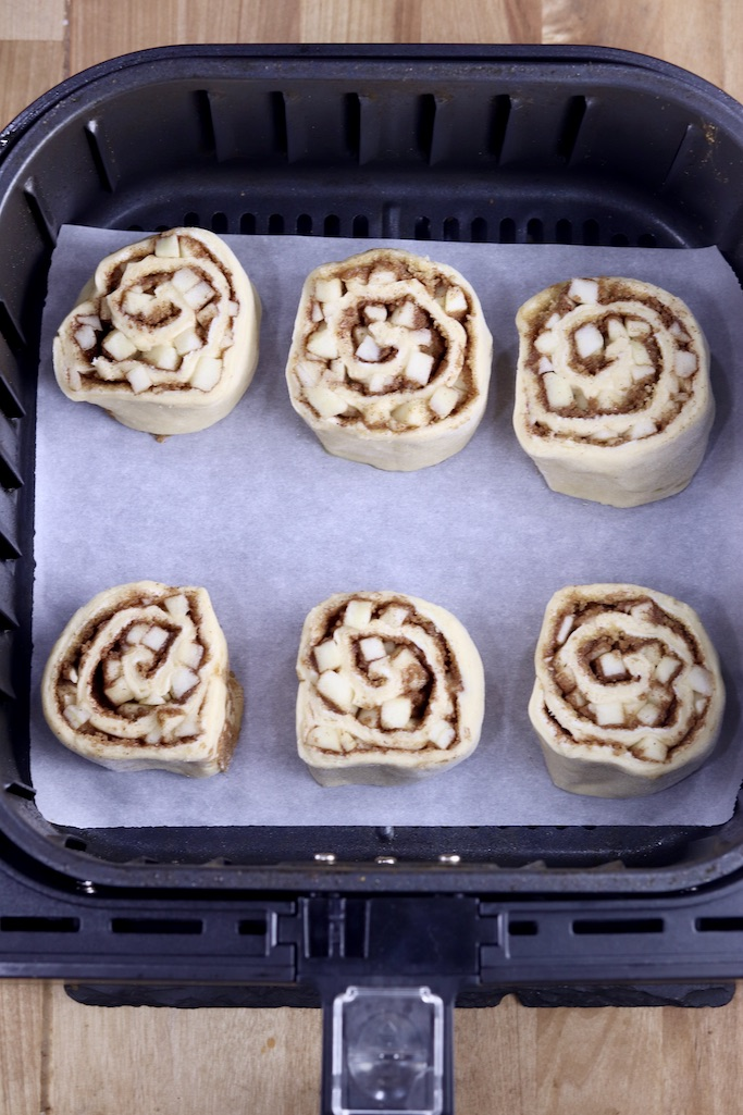 Air fryer basket lined with parchment, 6 uncooked cinnamon rolls