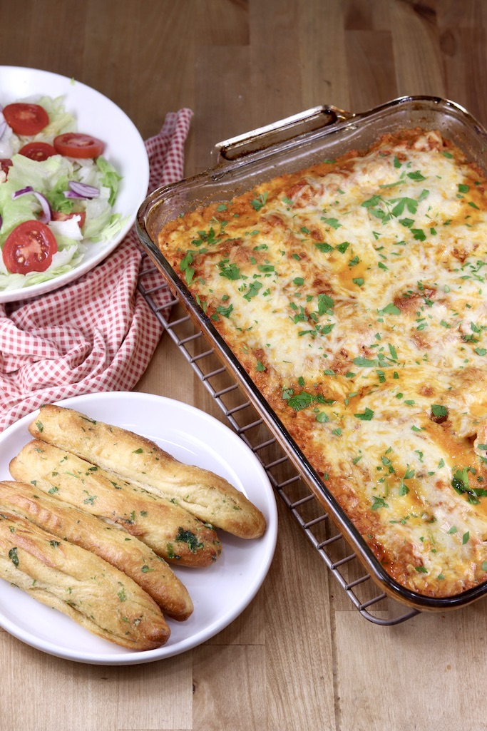 Pan of manicotti, breadsticks and a salad