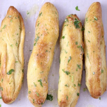 4 garlic butter breadsticks with parsley on parchment paper