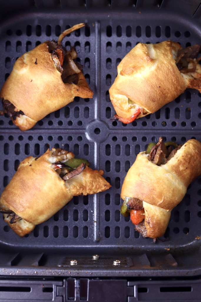 Air Fryer Cheesesteak Rolls in air fryer basket