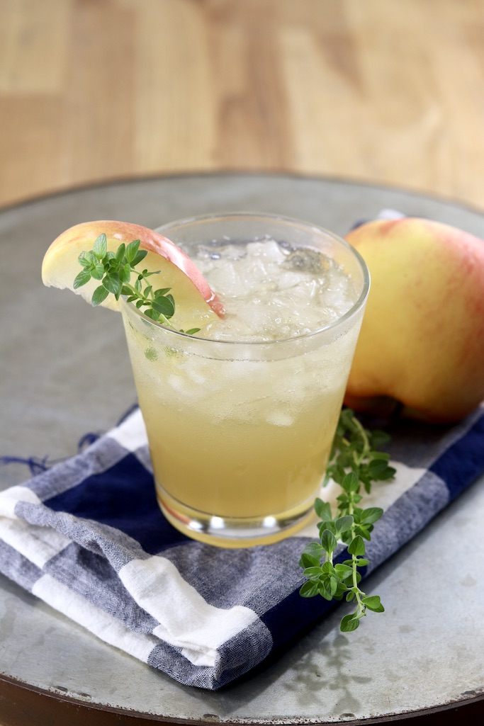 Apple Cider Cocktail with an apple and thyme garnish, on a tray with an apple and blue towel