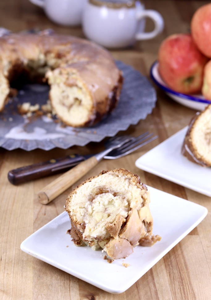 Apple Coffee Cake slice on a plate, cake on platter and bowl of apples behind it