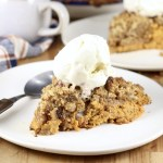 Pumpkin Pecan Crisp topped with ice cream on a white plate with spoon