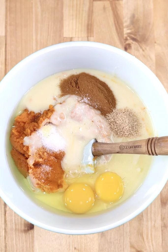 Bowl of pumpkin pie filling with eggs, pumpkin, cinnamon