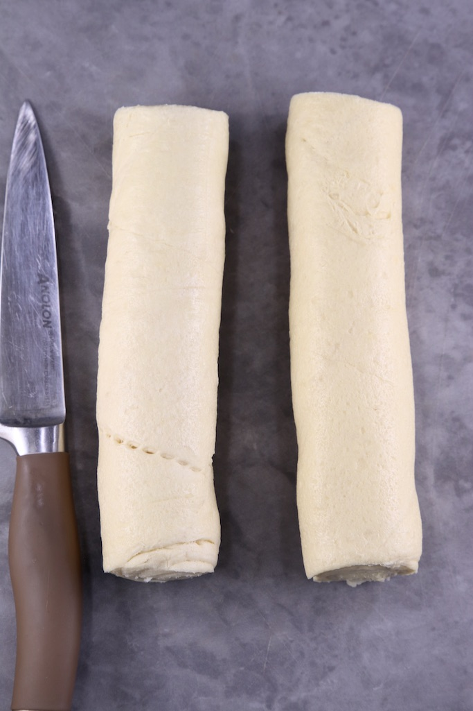 2 rolls of refrigerated crescent dough on a cutting board with a knife
