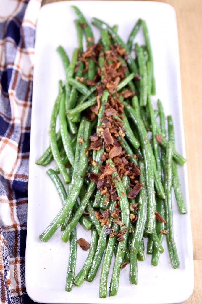 Rectangle white platter with cooked green beans topped with crispy crumbled bacon