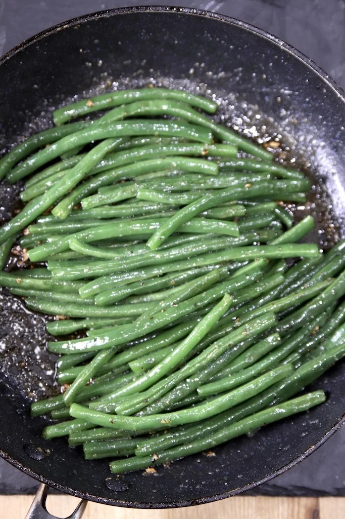 Green beans in a skillet with toasted garlic and brown sugar