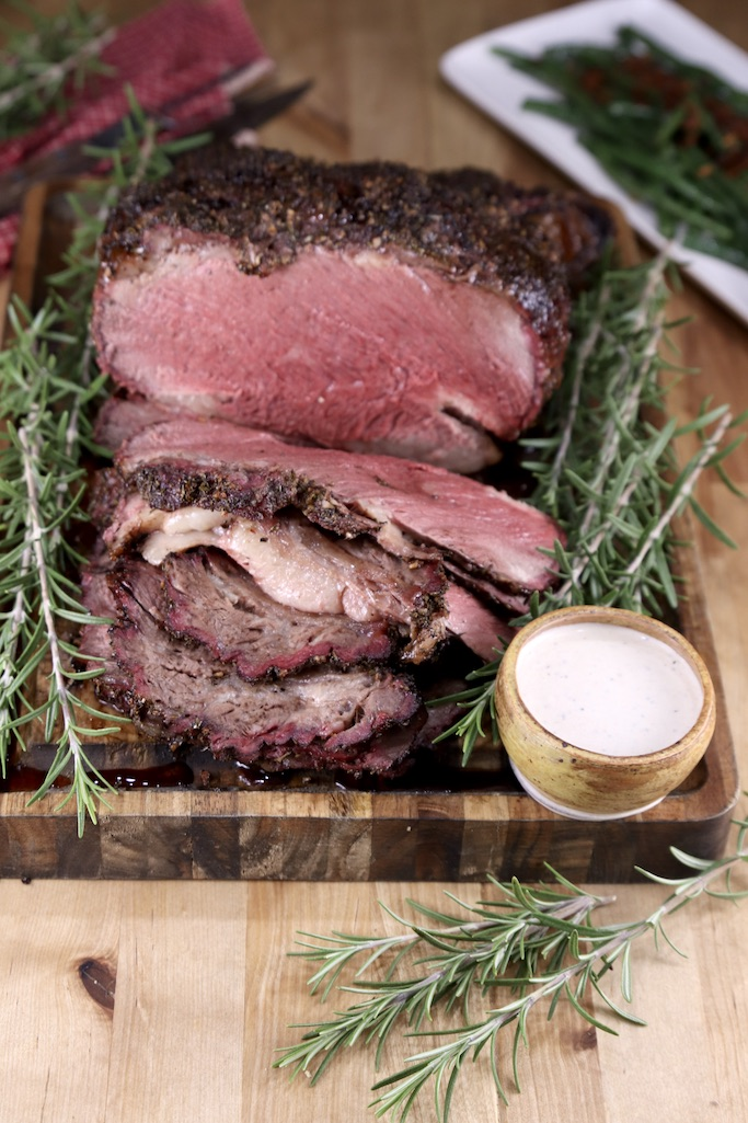 Overhead view of sliced prime rib roast with horseradish sauce, fresh rosemary, platter of green beans in background