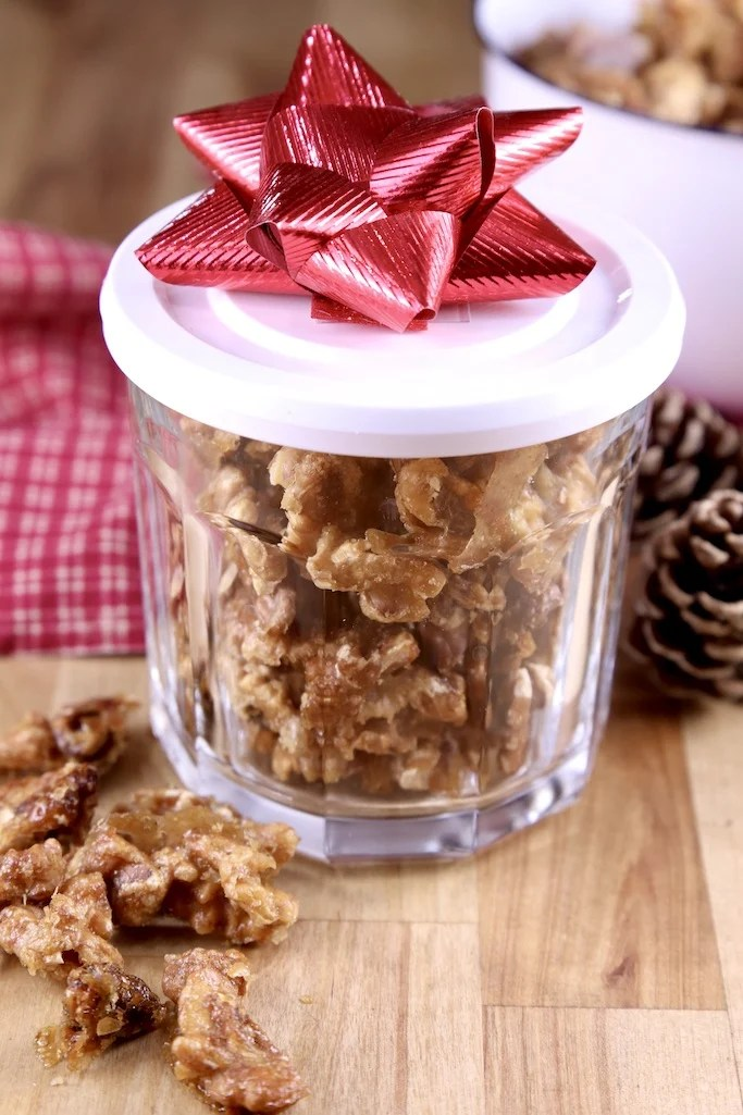 Candied walnuts in a lidded jar with a red bow for a holiday gift