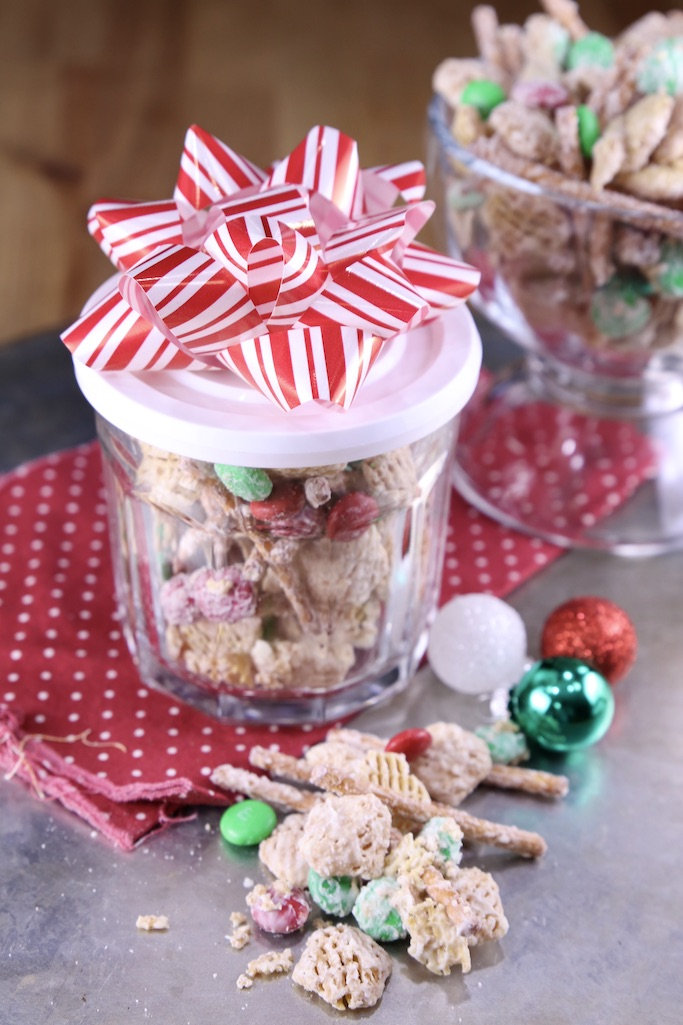 Small jar of white trash snack mix with a red and white bow. Snack mix scattered in front