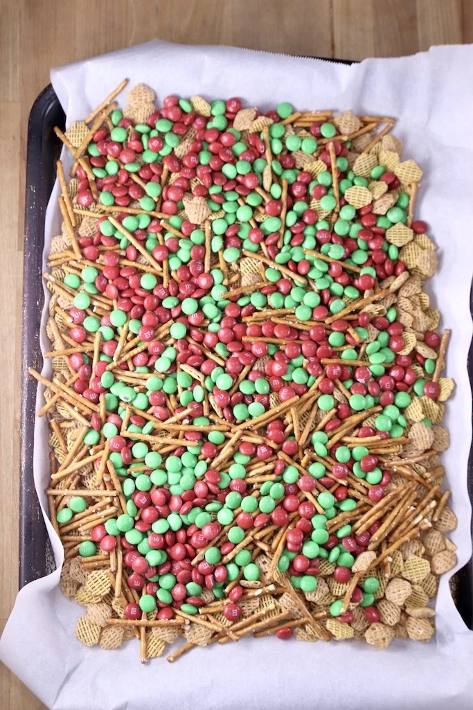 Parchment lined baking sheet with pretzels, cereal and m&m's