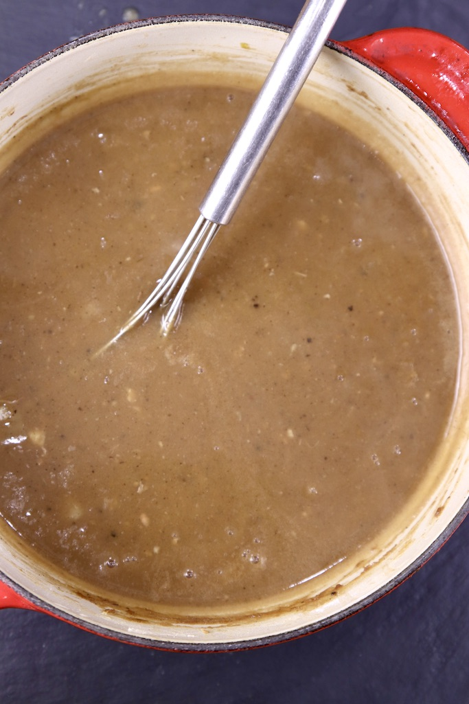 brown gravy in a saucepan with whisk