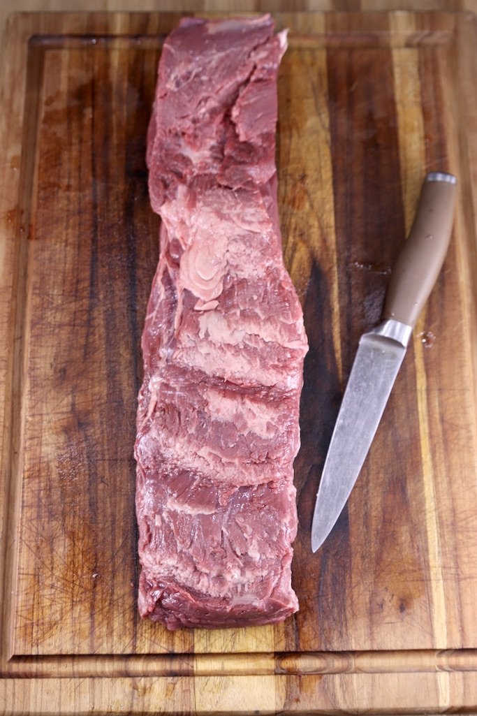 Trimmed Beef Tenderloin on a cutting board with a knife