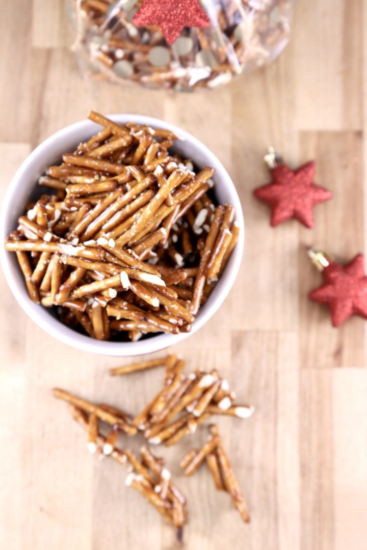 Candied Pretzels in a bowl with a few pieces scattered around. Star ornaments to the side.