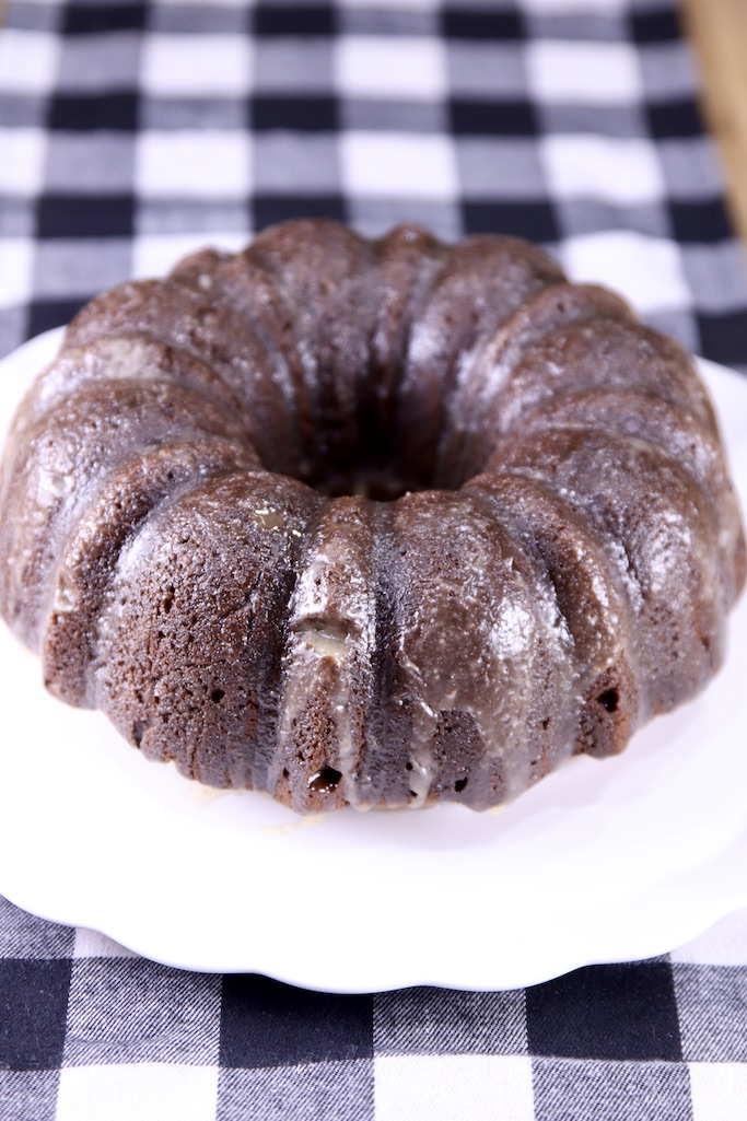 Chocolate Rum Bundt Cake with Buttered Rum Glaze on a serving plate on a black and white check runner