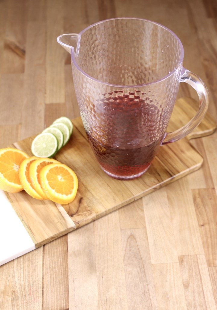 Pitcher with cranberry juice on a wood board with sliced oranges and limes