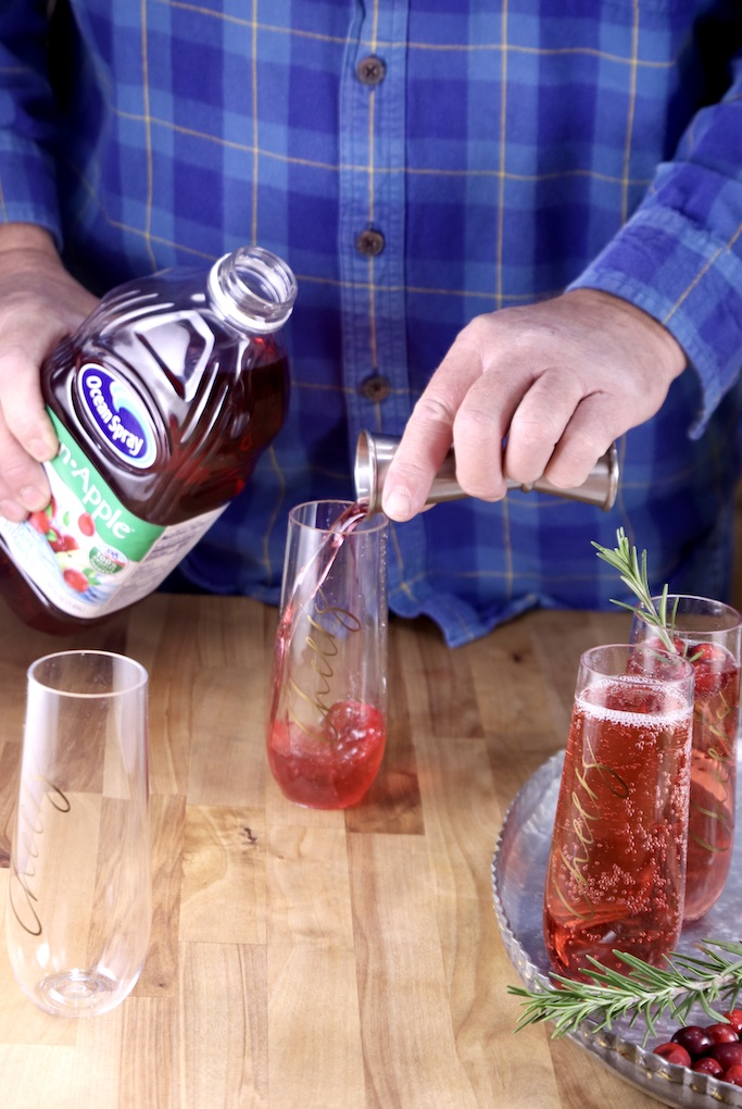 Man pouring cranberry juice into a champagne glass for cocktails