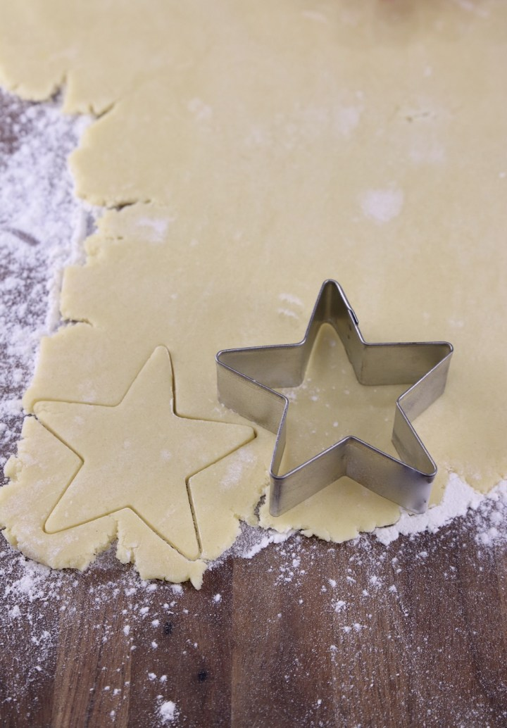 Cookie dough rolled out cutting out with a star cookie cutter