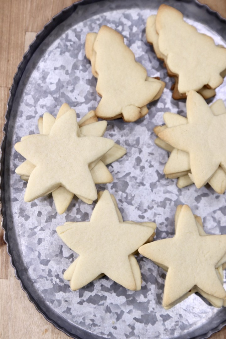 Tray of cut out sugar cookies stacked. Stars and tree shapes.