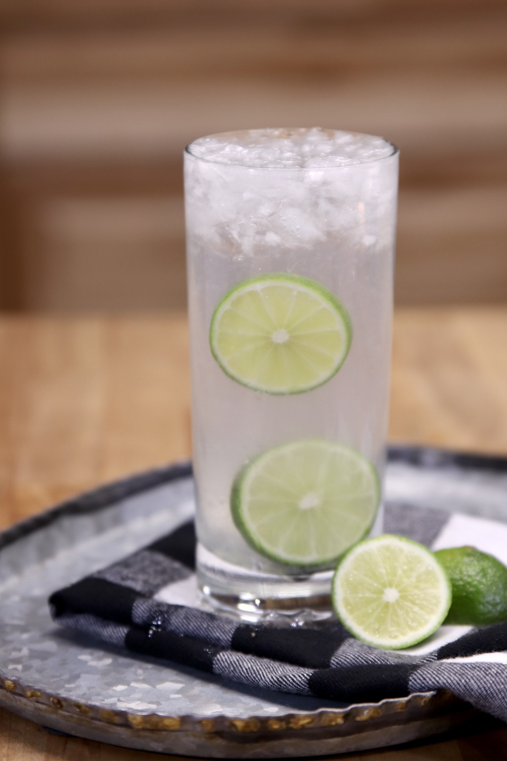 Gin Rickey Cocktail in a tall glass with 2 slices of lime for ganish