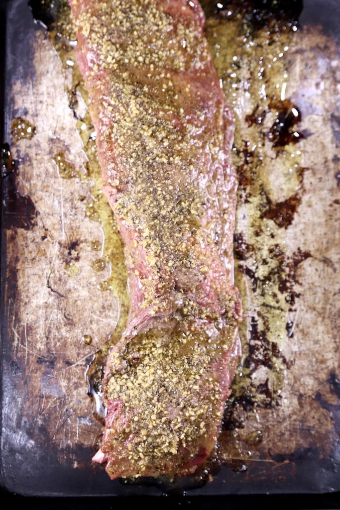 sheet pan with beef tenderloin coated in garlic butter