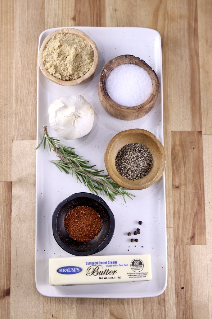 Ingredients for beef tenderloin garlic butter crust on a white plate: butter, red pepper, black pepper, salt, head of garlic, brown sugar and sprig of rosemary