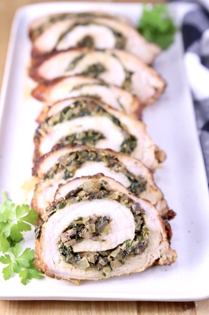 Stuffed Pork Tenderloin on a platter, closeup view of slices