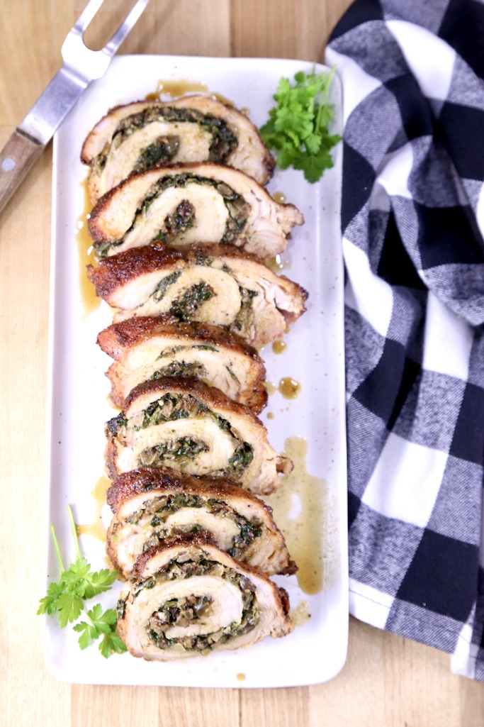 Stuffed Pork Tenderloin on a platter with a blue check napkin to the side