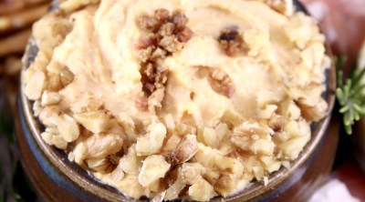 Bacon beer cheese dip with walnut garnish in a bowl