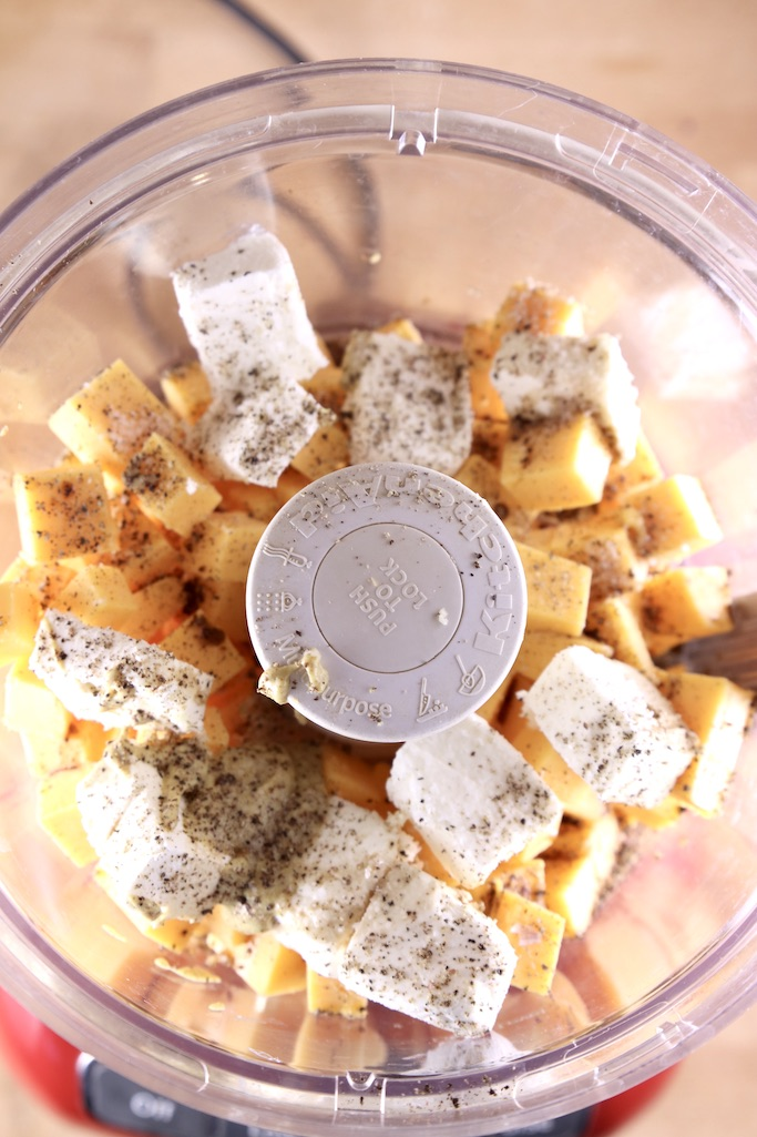 Food processor with chunks of cream cheese, cheddar cheese and spices