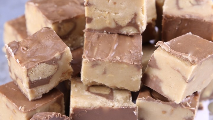 Peanut Butter Cup Fudge stacked on a polka dot baking sheet