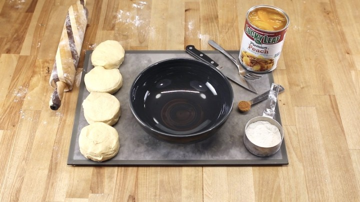 Cutting board with can biscuits, a black bowl, rolling pin, can of peach pie filling, spoon of cinnamon, flour