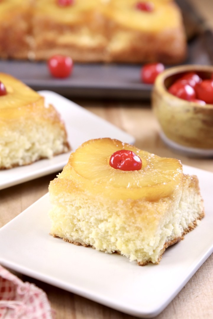 Slice of pineapple upside down cake on a small plate, bowl of cherries, platter of cake in background