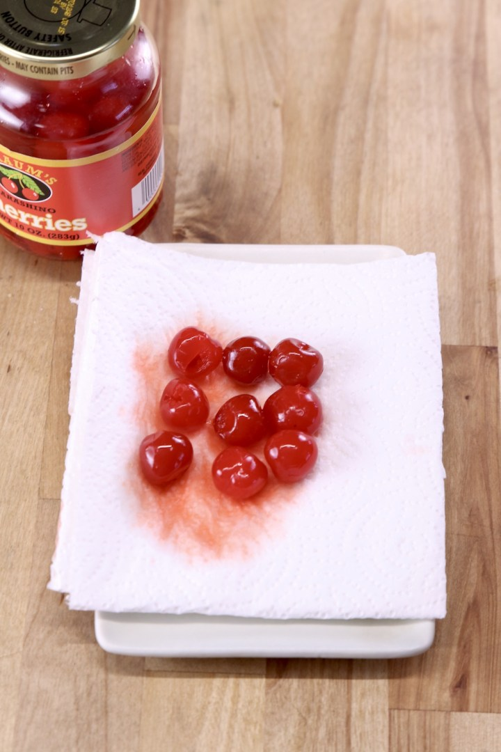 maraschino cherries draining on a paper towel with jar of cherries to the side