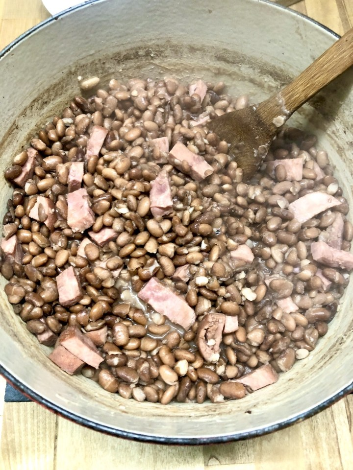 Pinto Beans with ham in a dutch oven with wooden spoon