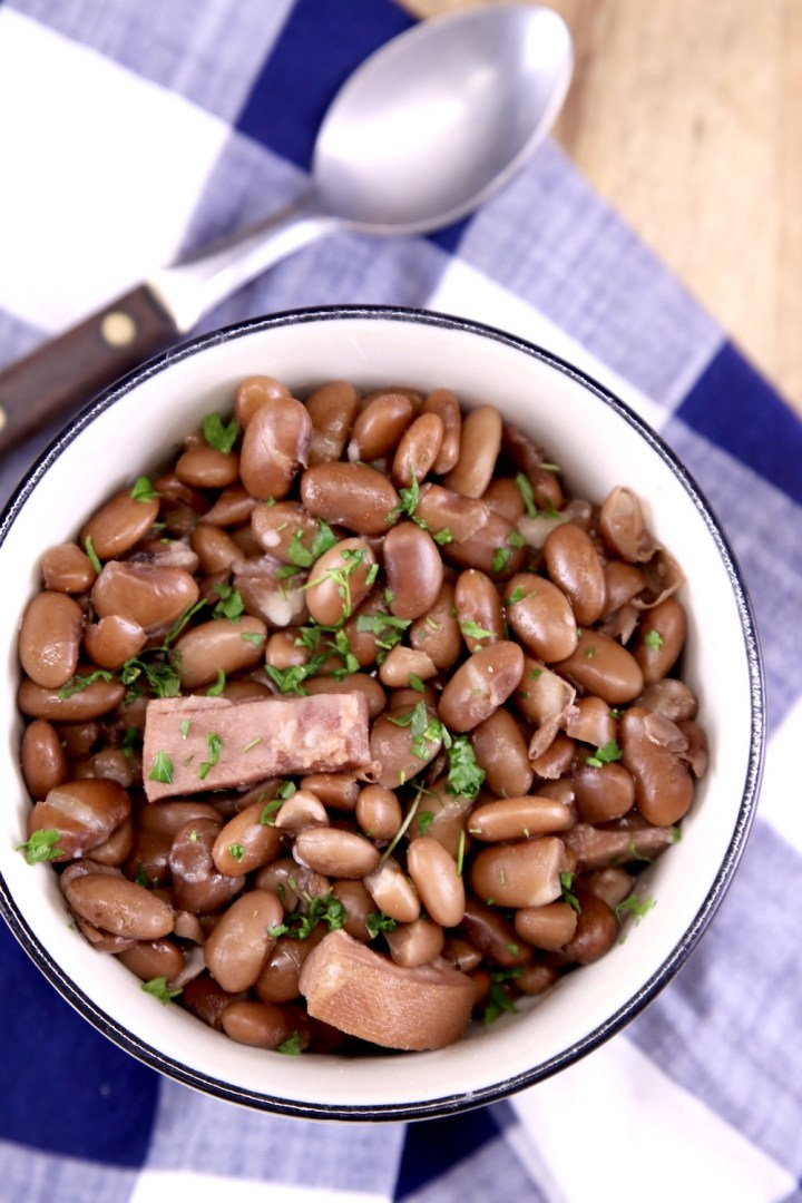 Pinto Beans with ham in a bowl with a spoon next to the bowl