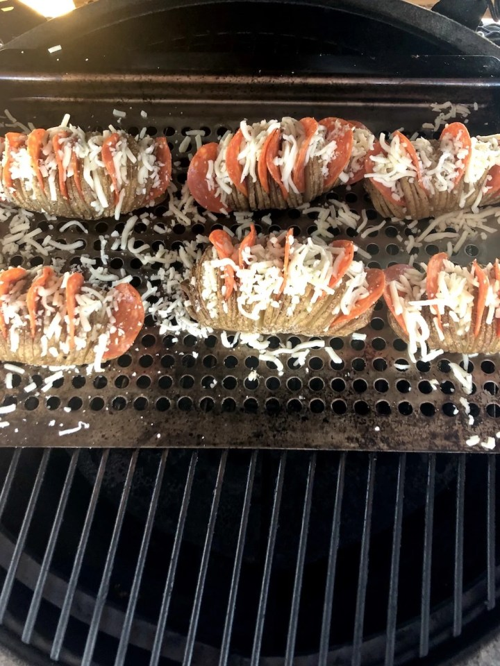 Grill pan of pizza stuffed potatoes on a grill