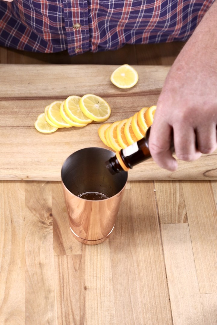 adding bitters to a cocktail shaker